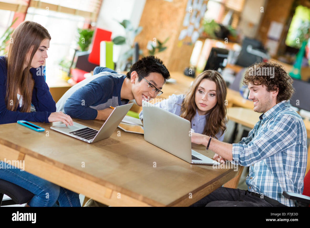 Group Of Young Attractive Happy People Working Together At The Table