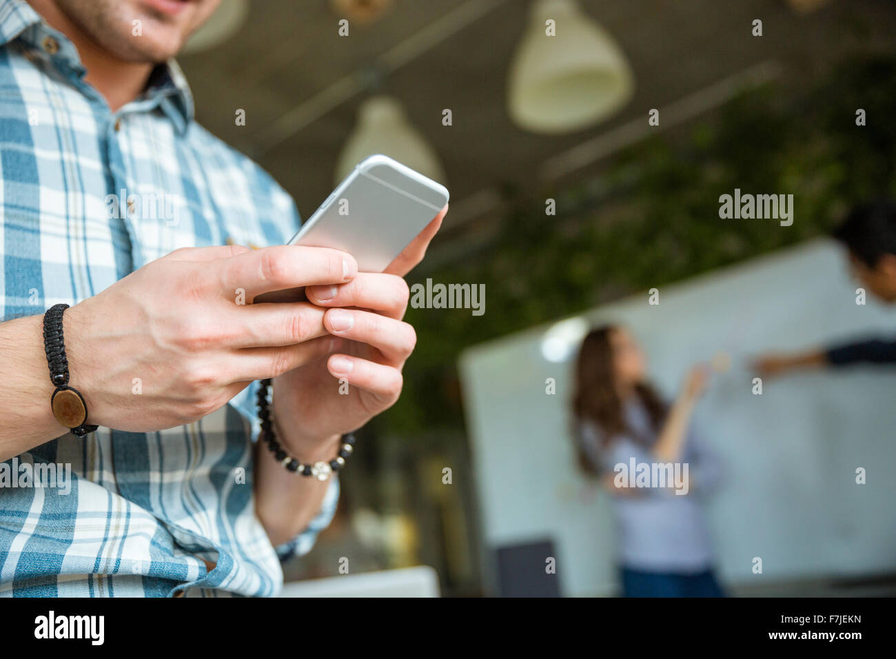 Closeup of hands of young man in checkered shirt using mobile phone while his partners arguing - Stock Image