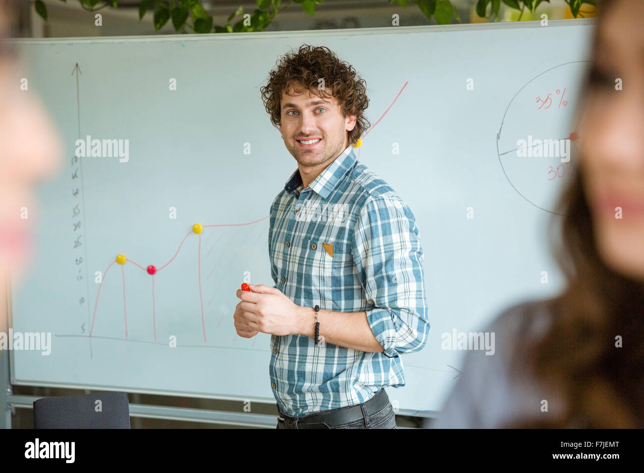 Handsome smart successful positive curly guy in checkered shirt standing near the whiteboard and smiling - Stock Image