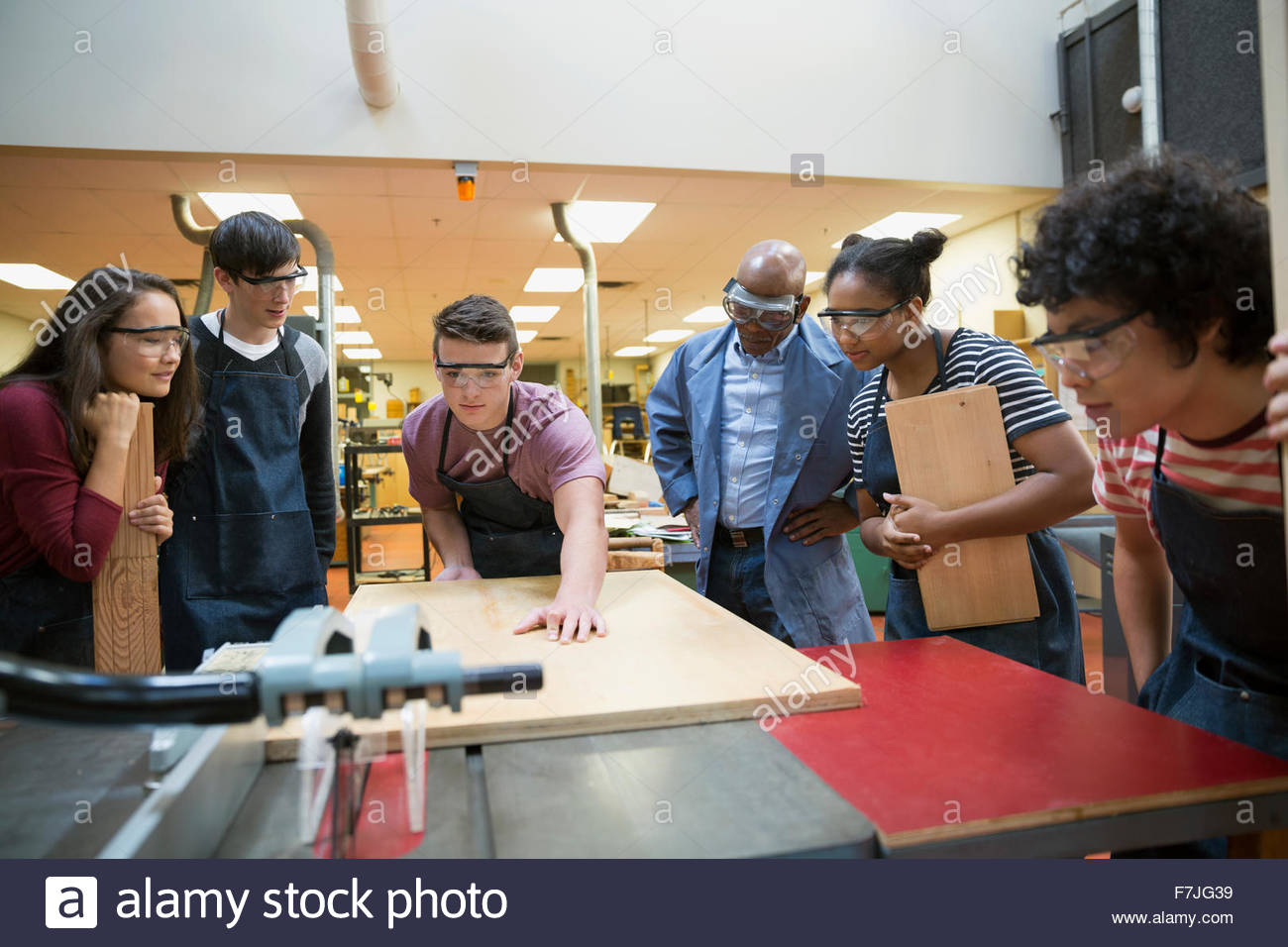 High school students watching classmate at woodcutting machine - Stock Image