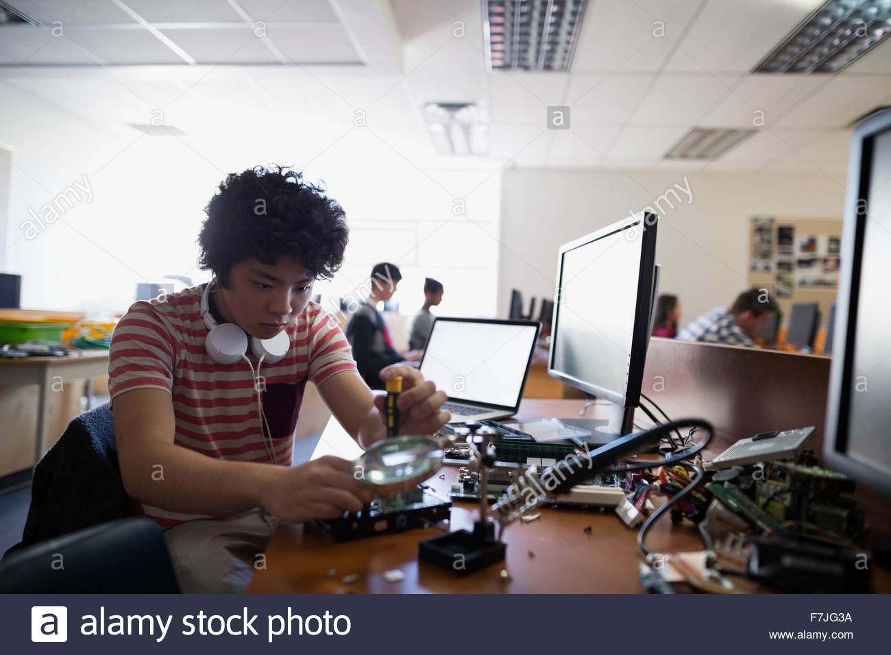 Focused high school student fixing computer part - Stock Image