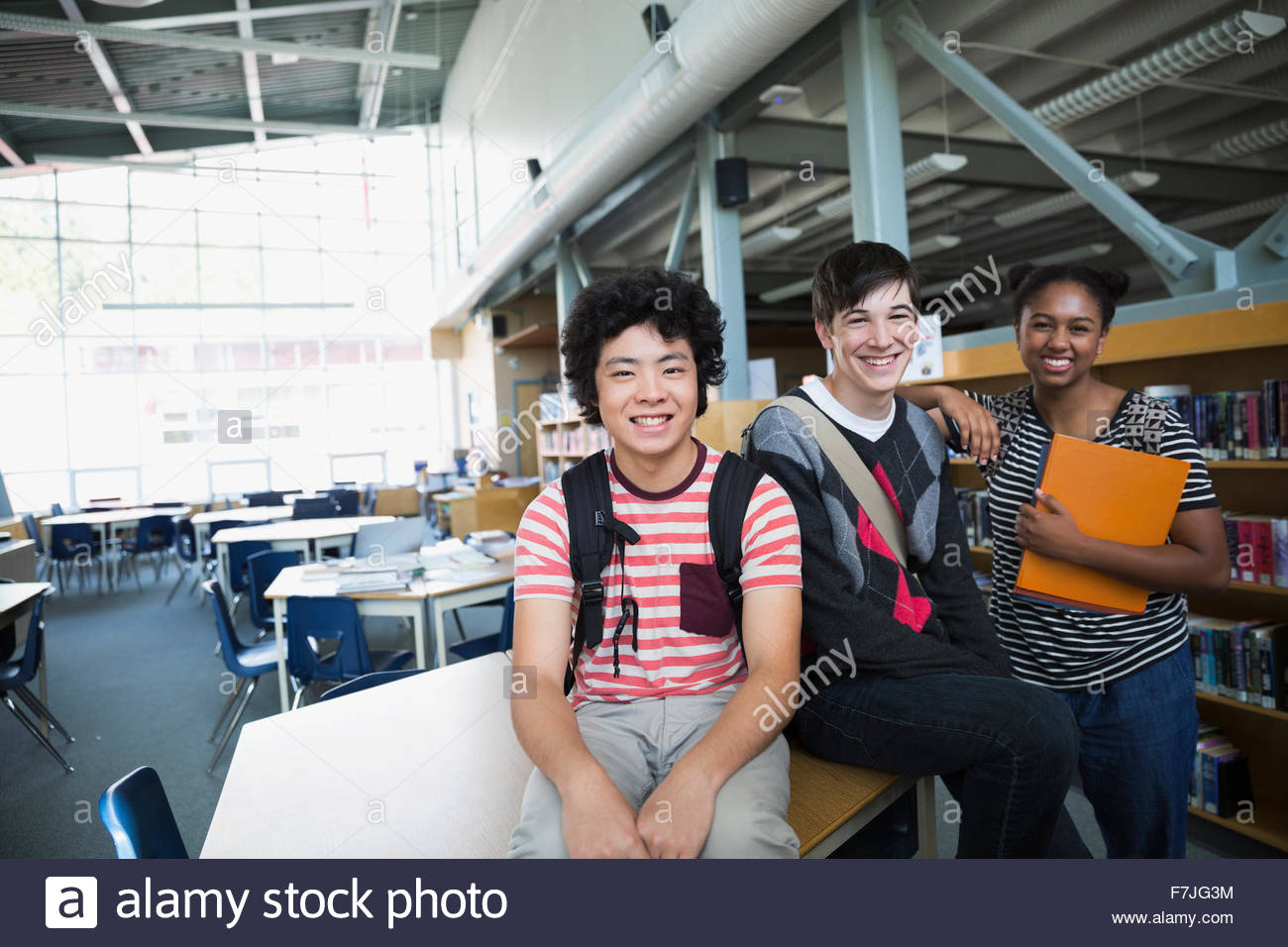 Portrait confident high school students in library - Stock Image
