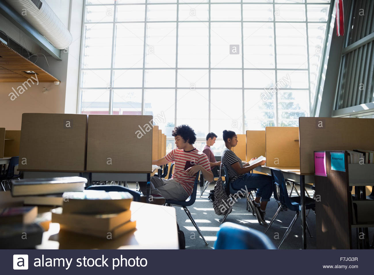 High school students studying in library - Stock Image