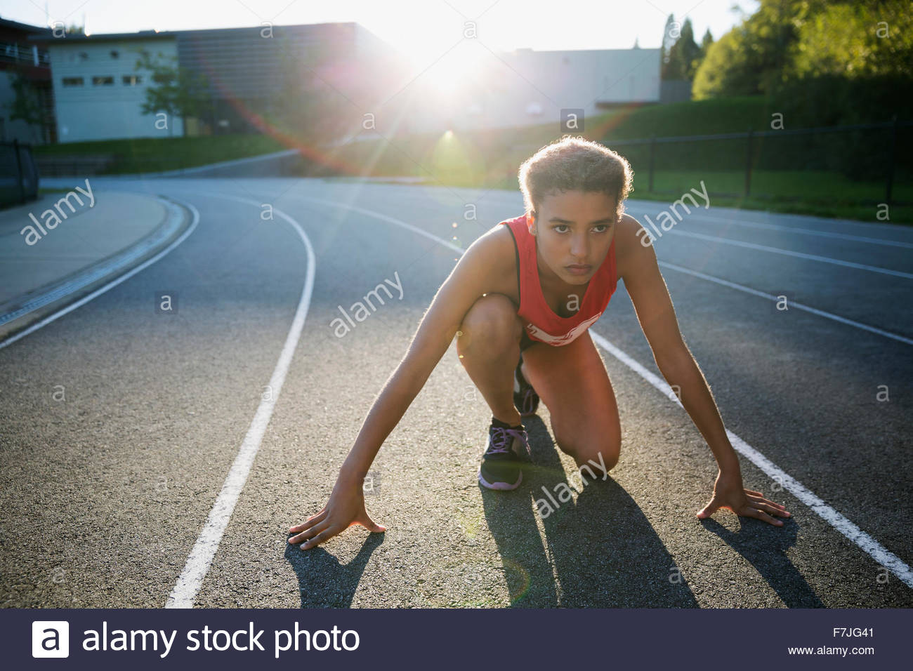 Focused high school track and field athlete ready - Stock Image