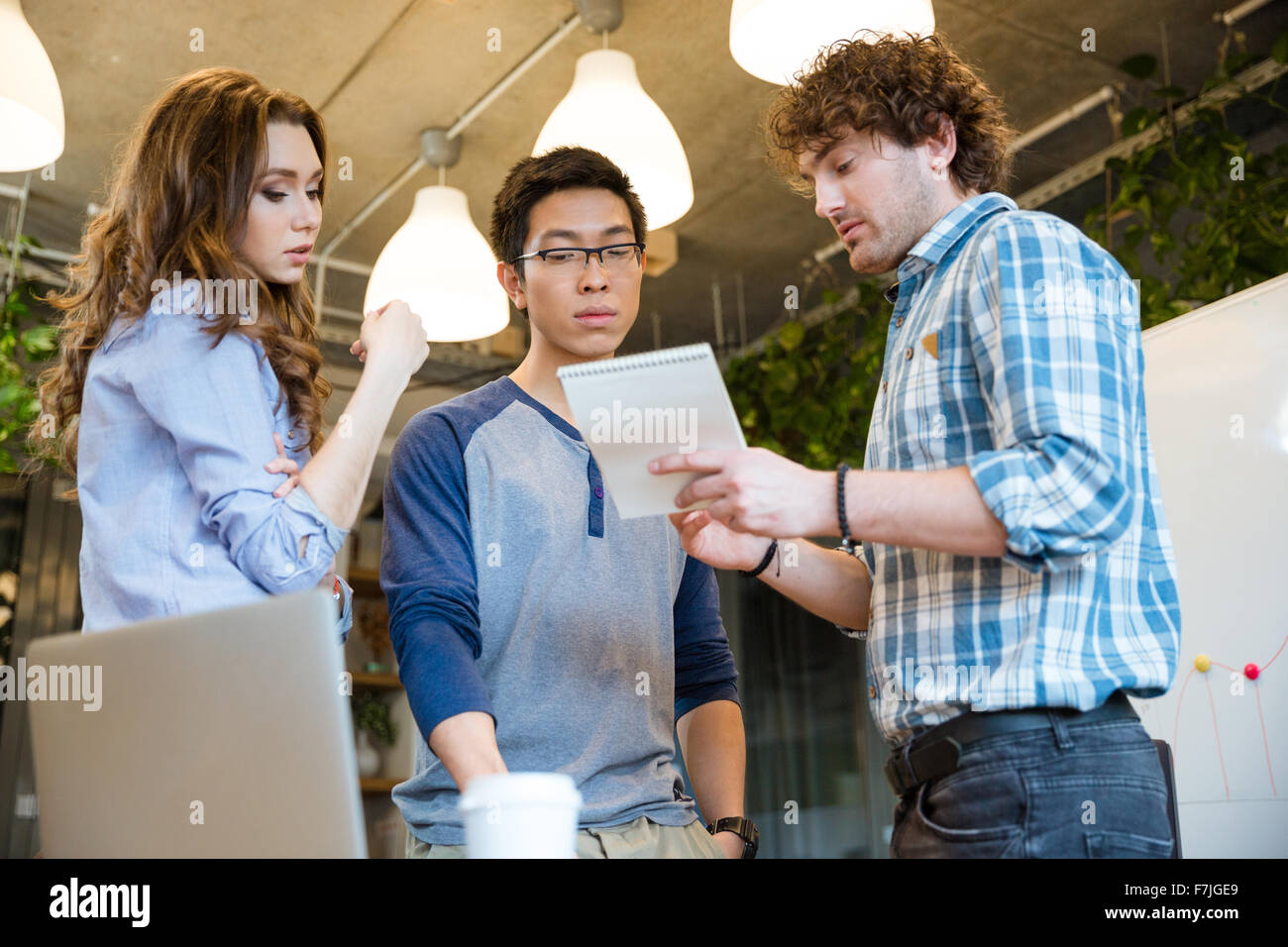 Smart attractive young man sharing his ideas with concentrated coworkers - Stock Image