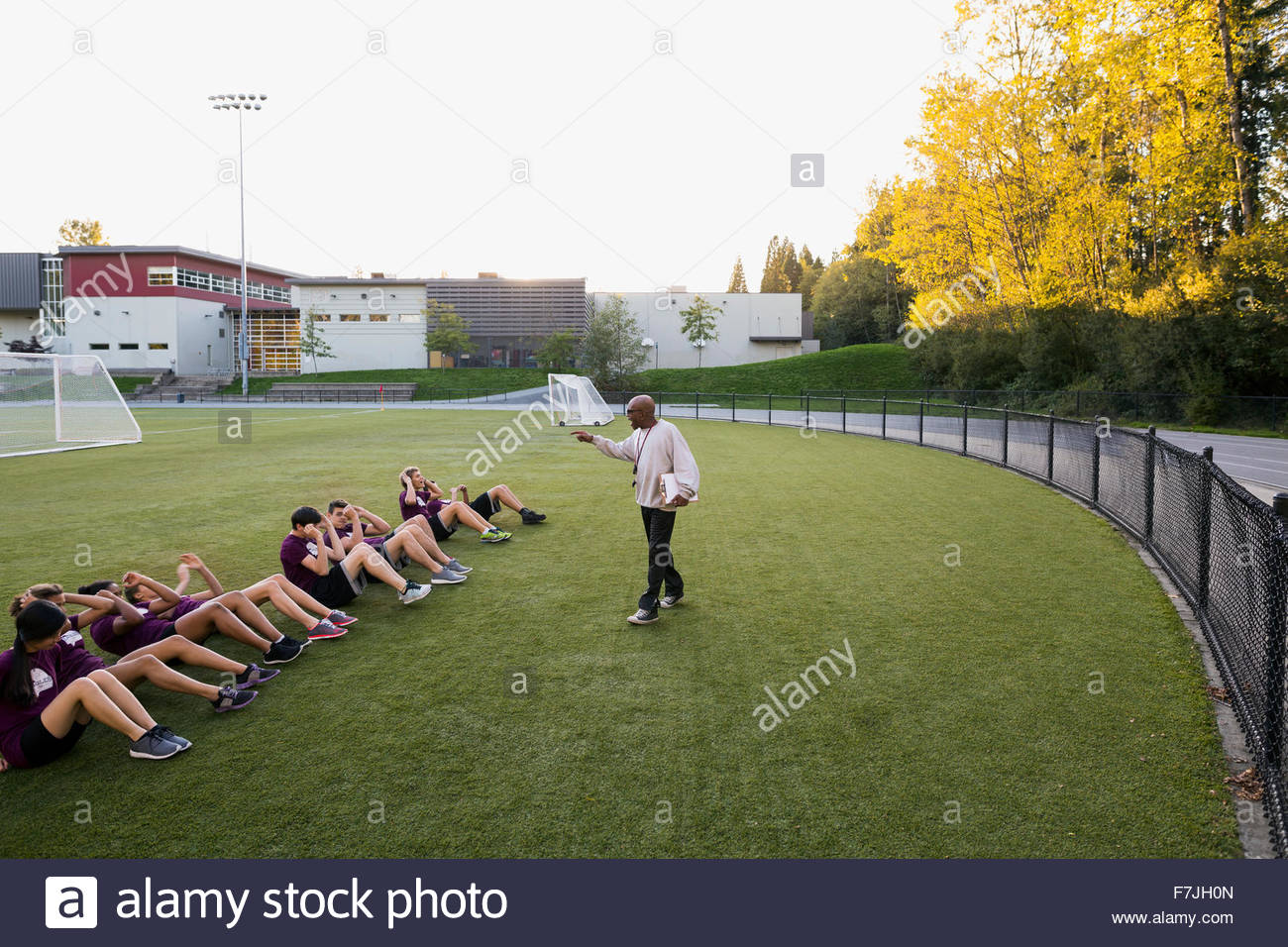 High school physical education teacher students sit-ups - Stock Image