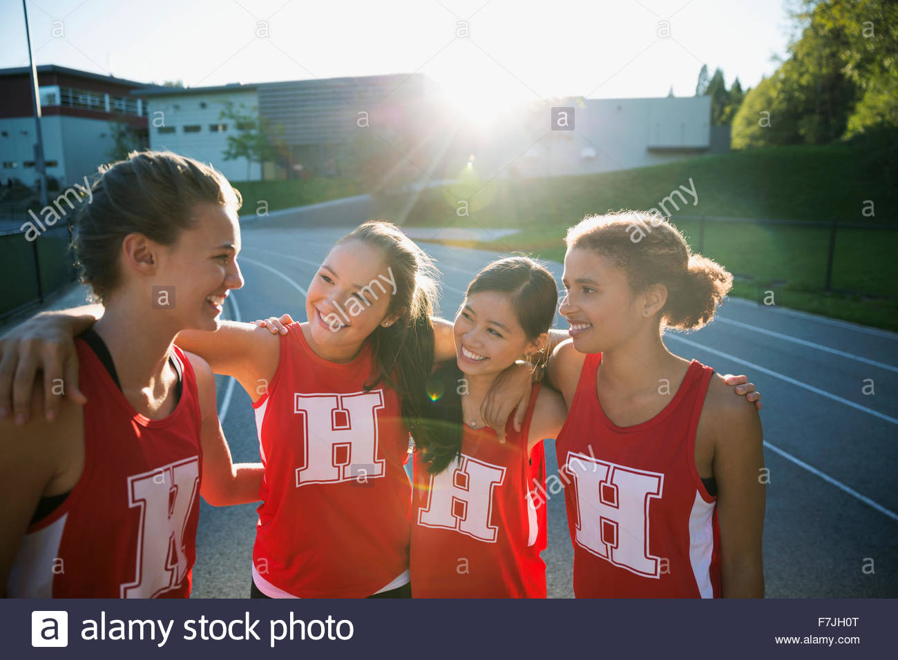 Female high school track and field athletes hugging - Stock Image