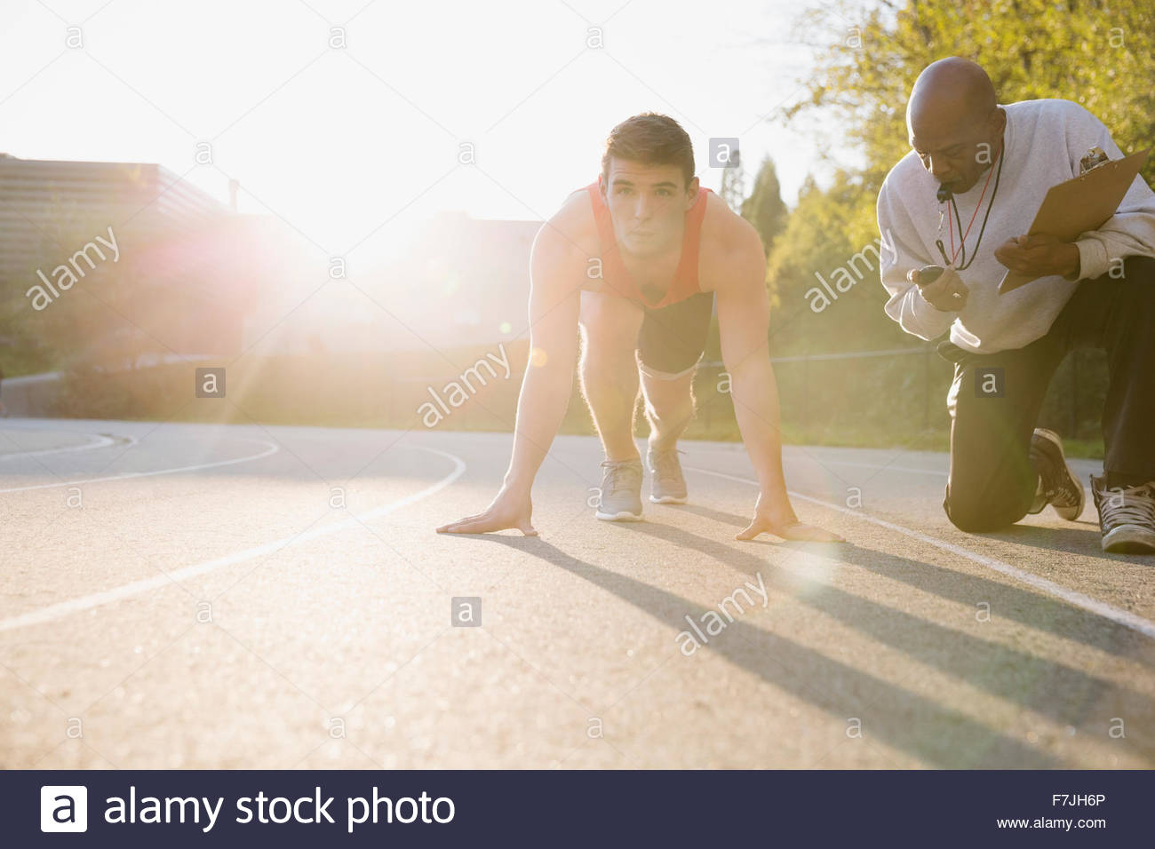 Coach timing high school track and field athlete - Stock Image