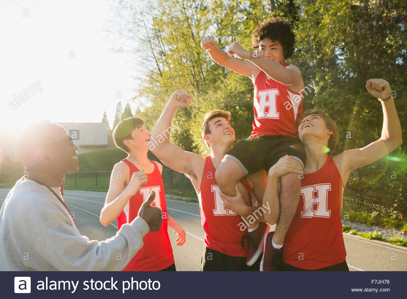 Enthusiastic high school track and field team celebrating - Stock Image