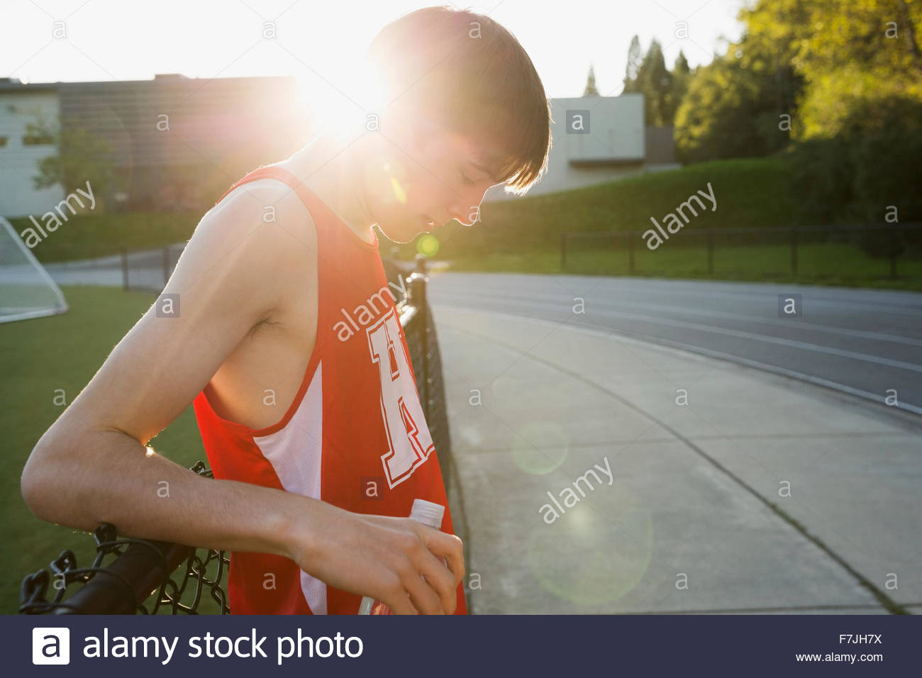 High school track and field athlete resting - Stock Image
