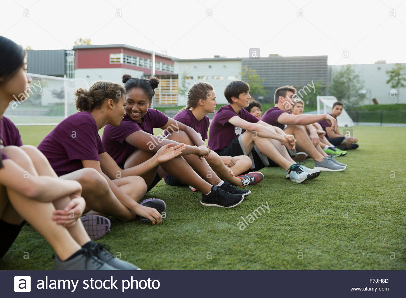 High school students sitting a row physical education - Stock Image