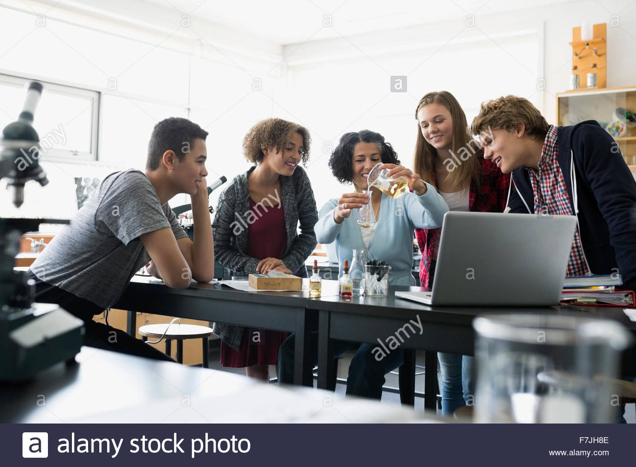 High school students and teacher conducting scientific experiment - Stock Image