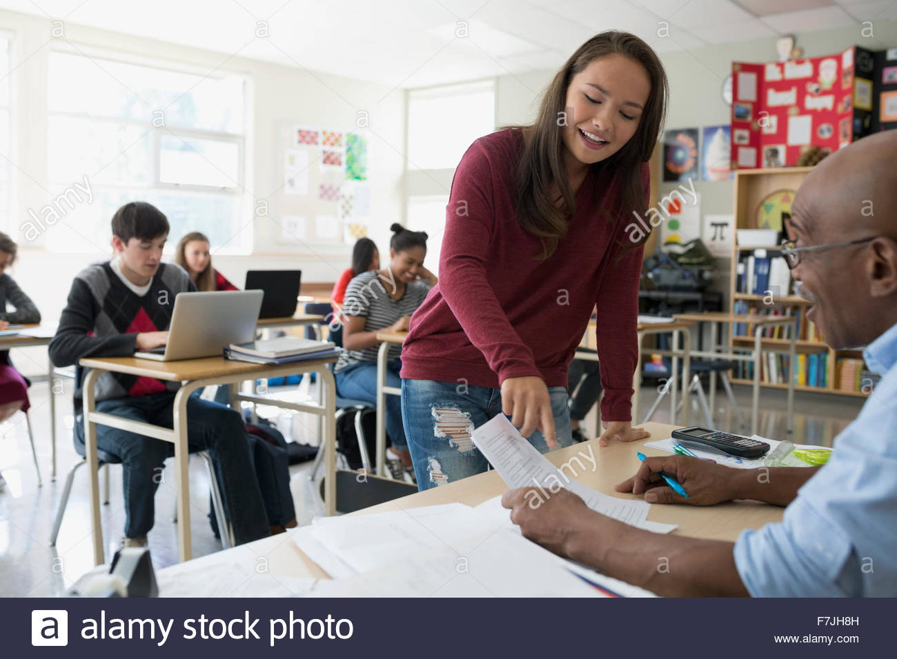 High school student discussing homework with teacher classroom - Stock Image