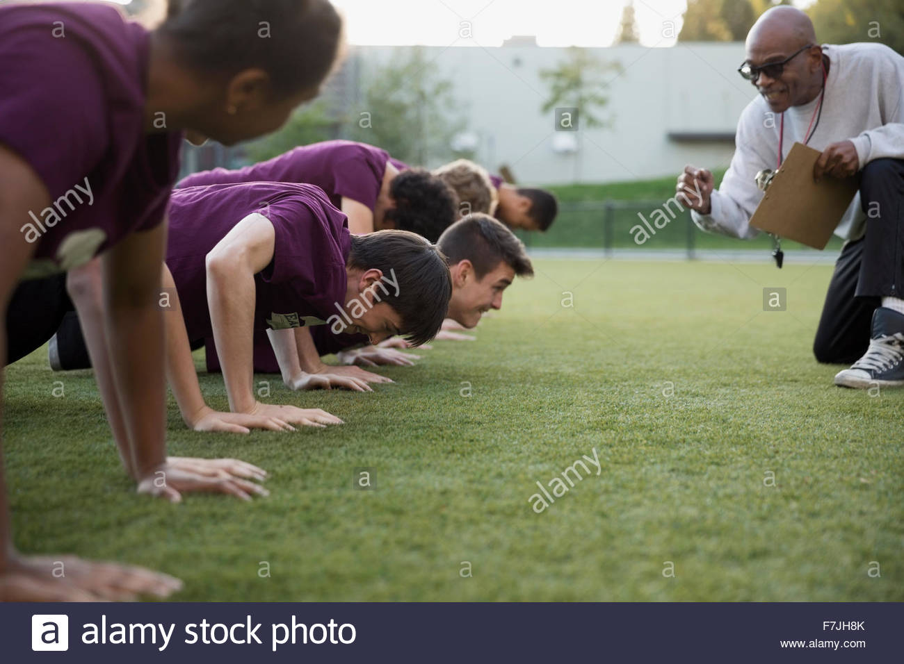 Physical education teacher encouraging students doing push-ups - Stock Image