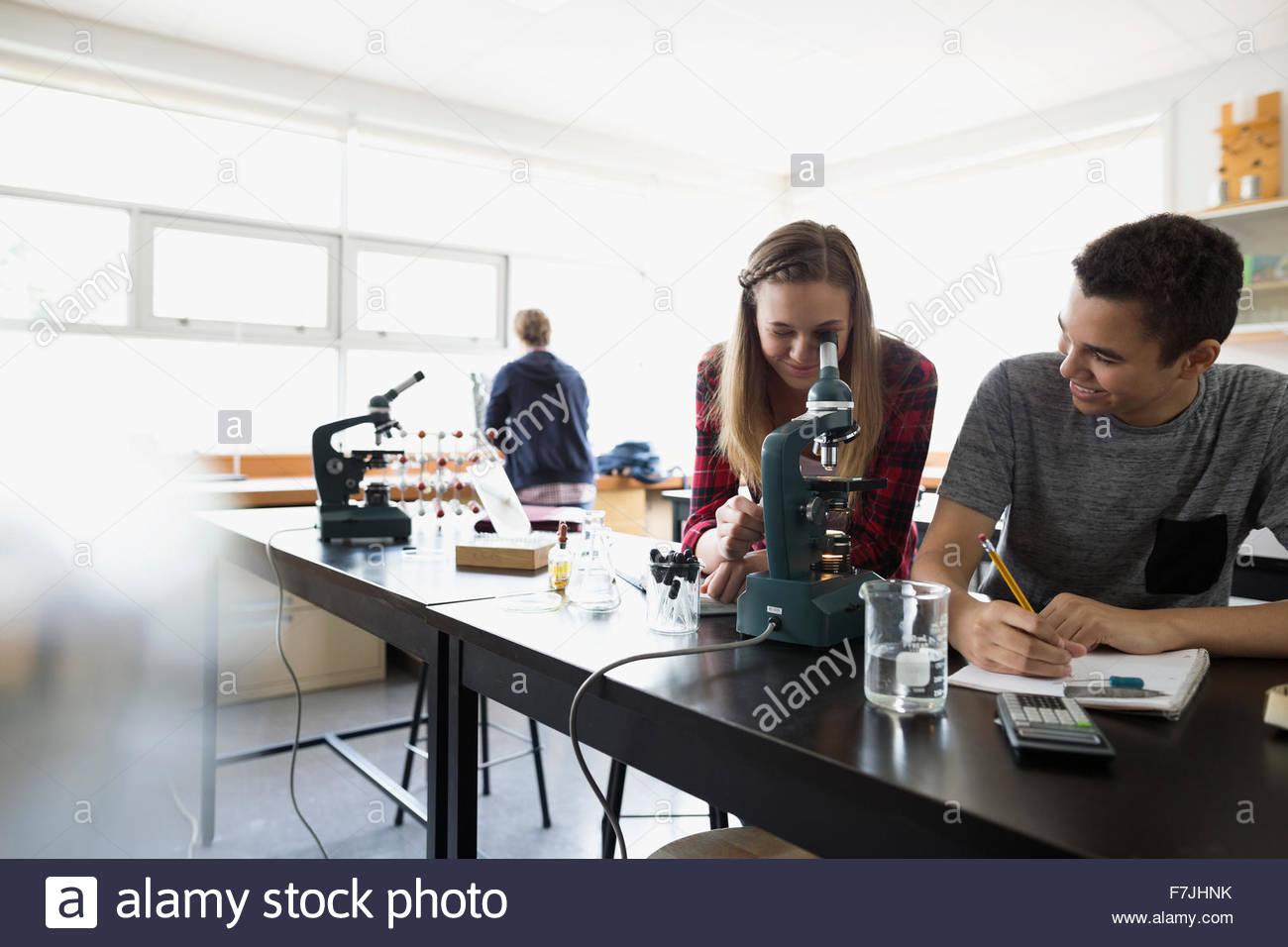 High school students using microscope science laboratory classroom - Stock Image