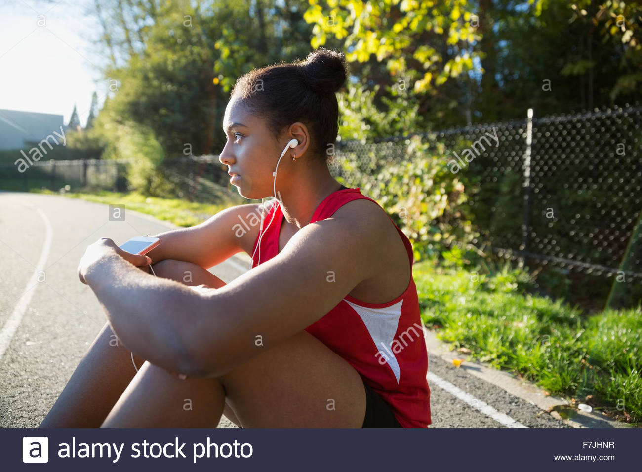 Serious high school athlete listening music running track - Stock Image