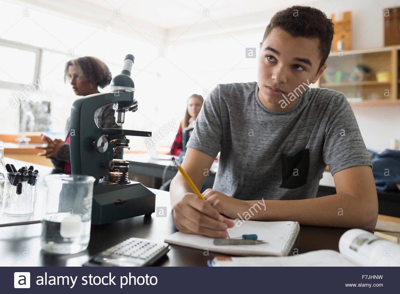 Focused high school student taking notes science class - Stock Image