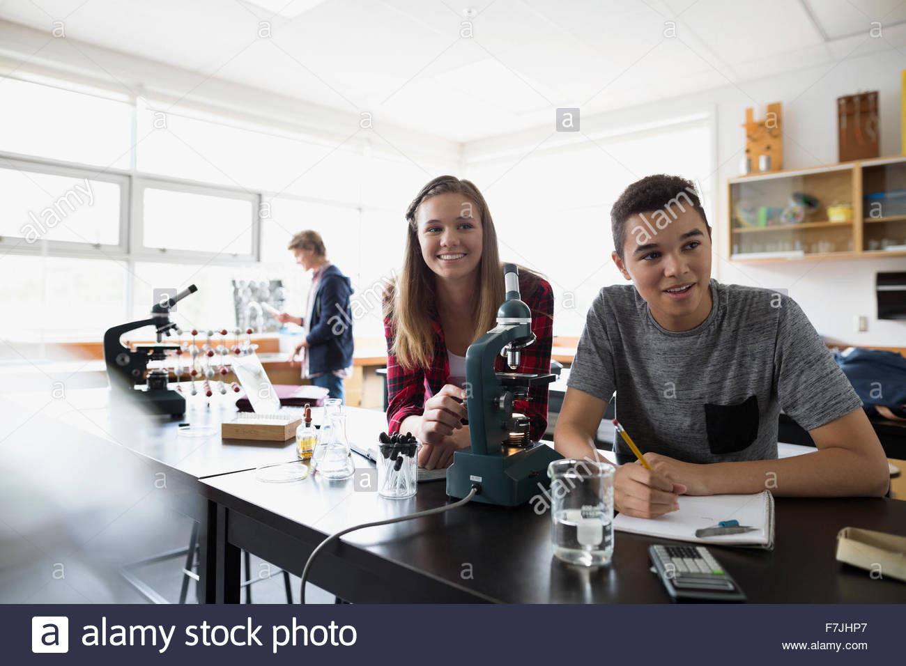 High school students at microscope science laboratory classroom - Stock Image