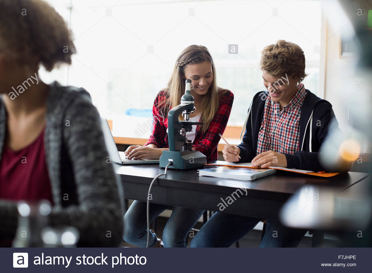 High school students taking notes at microscope - Stock Image