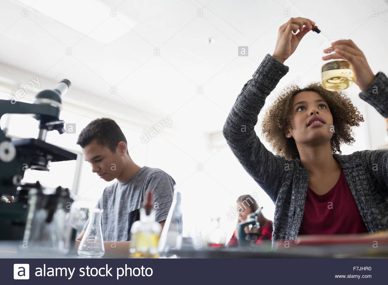 High school student dropping liquid into beaker - Stock Image