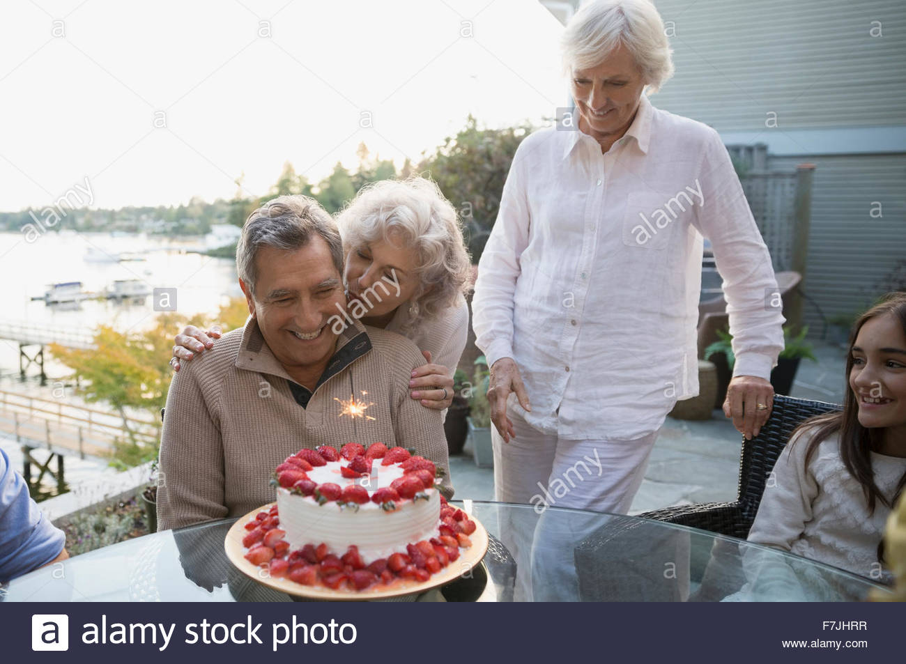 Wife hugging husband with strawberry birthday cake patio - Stock Image