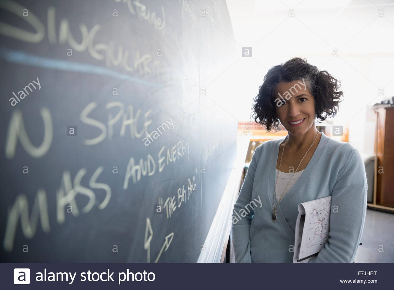 Portrait confident teacher at blackboard in classroom - Stock Image