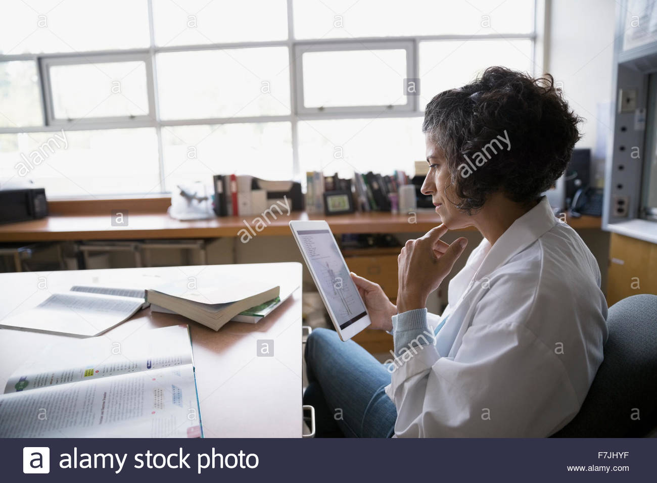 Focused teacher using digital tablet at desk - Stock Image