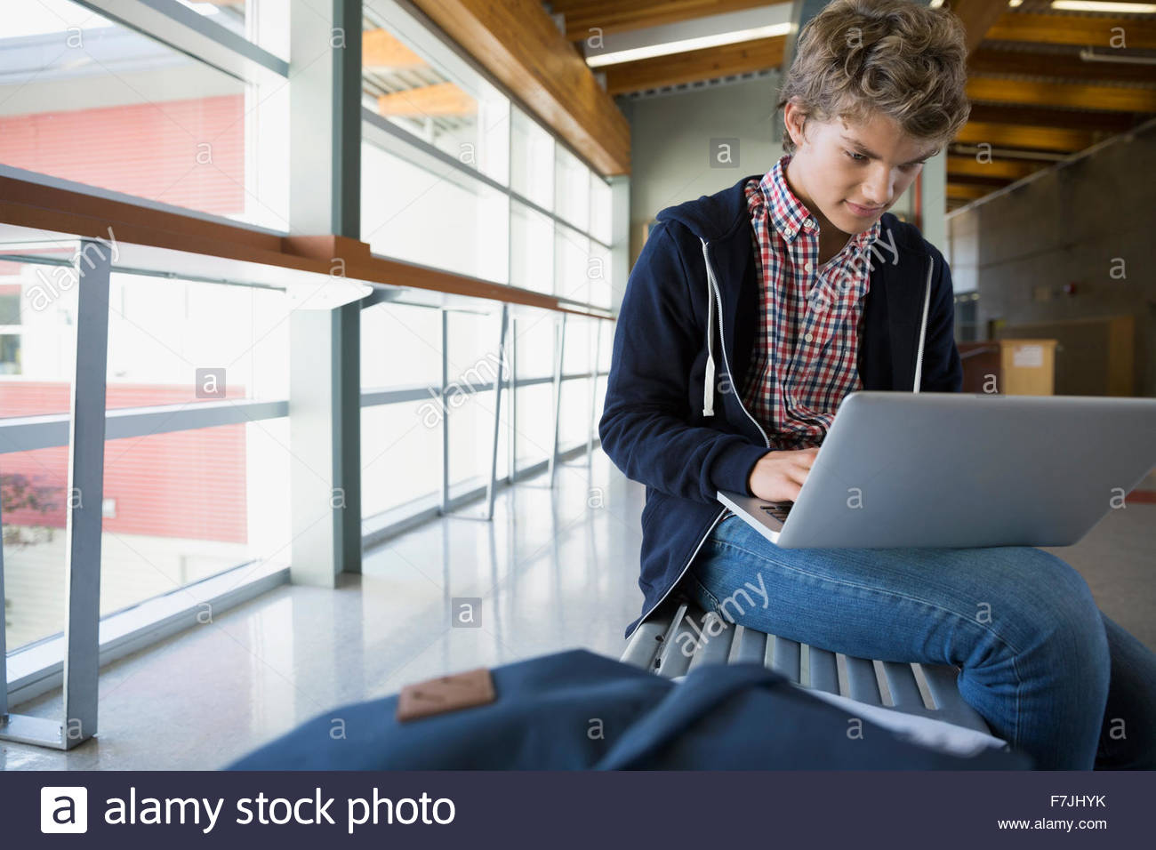 High school student using laptop on bench - Stock Image