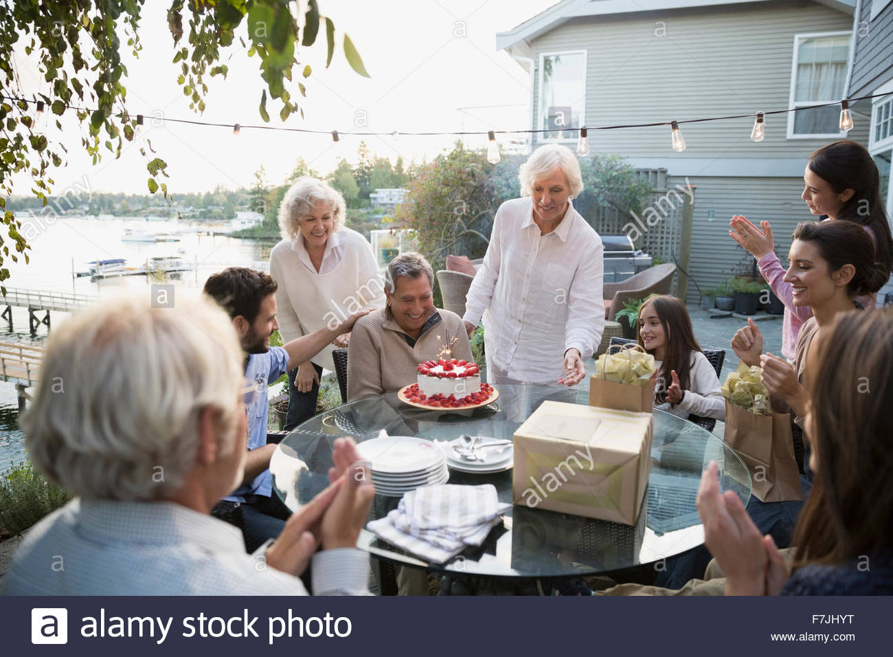 Senior man celebrating birthday family cake lakeside patio - Stock Image
