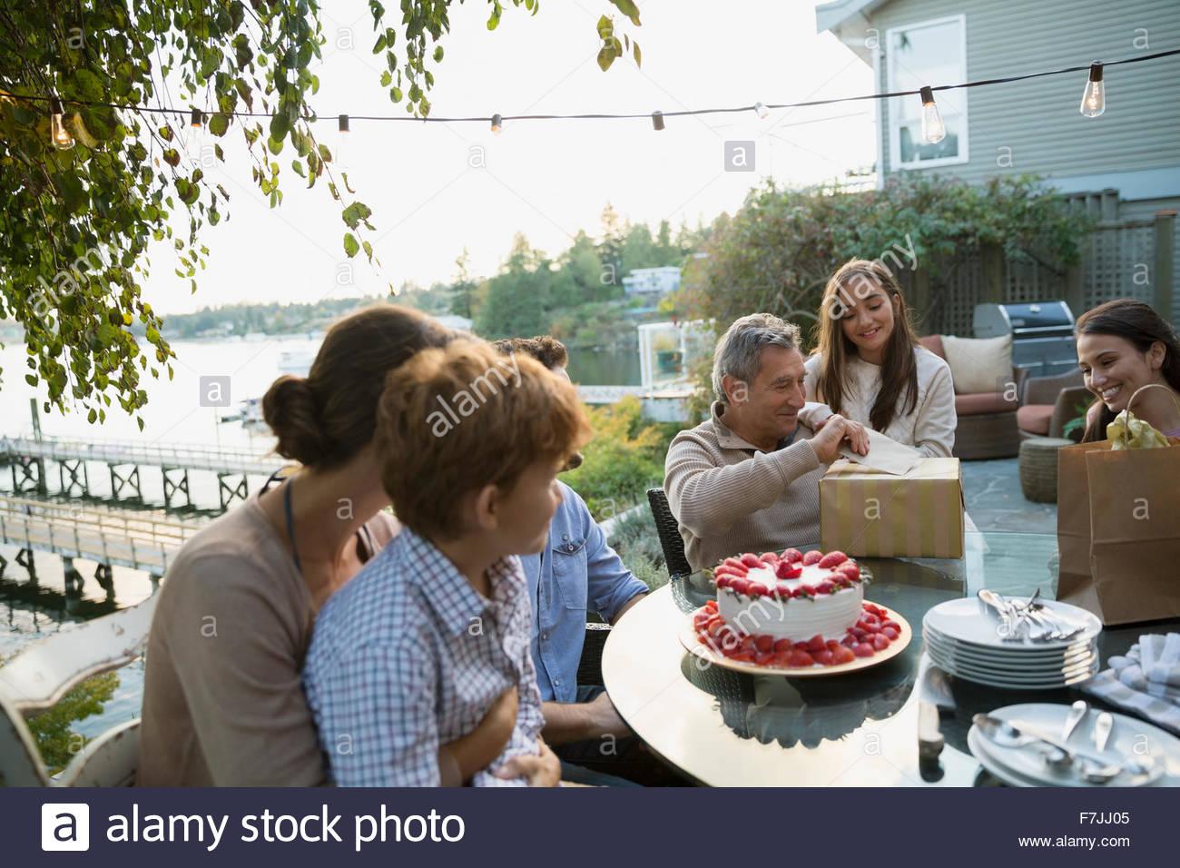 Senior man opening birthday gifts family lakeside patio - Stock Image