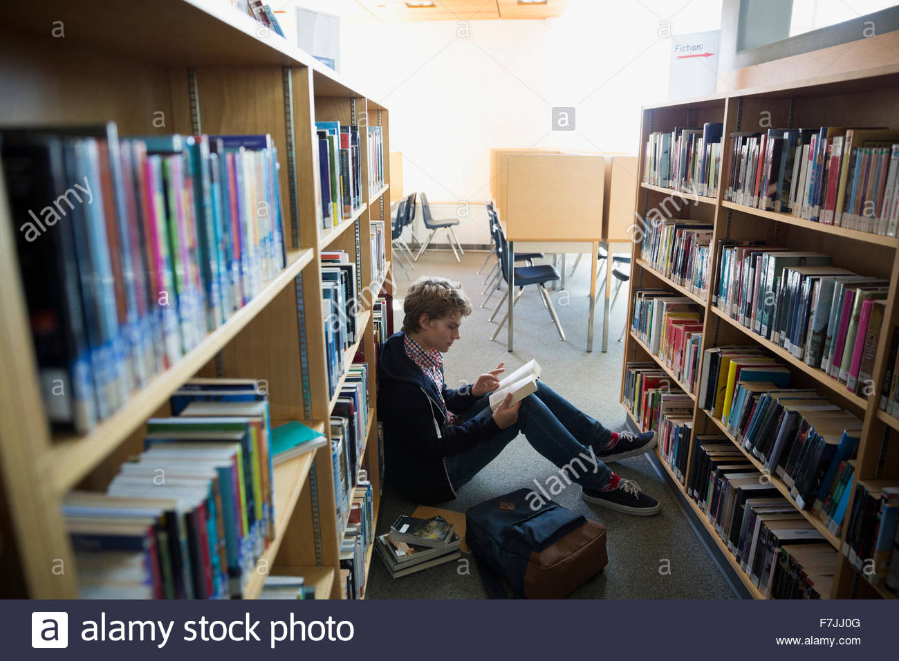 High school student reading book on library floor - Stock Image