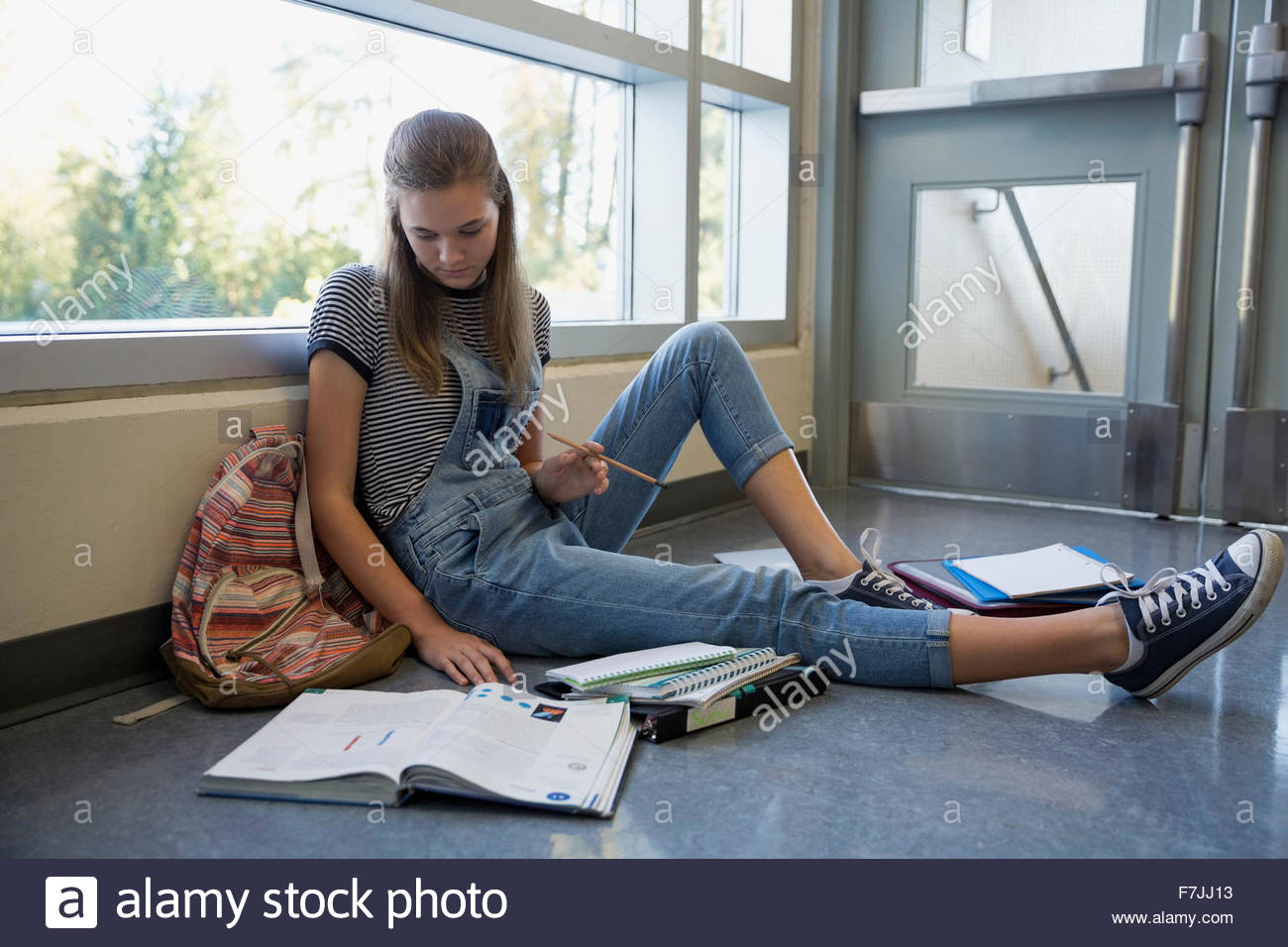 High school student with textbook studying on floor - Stock Image
