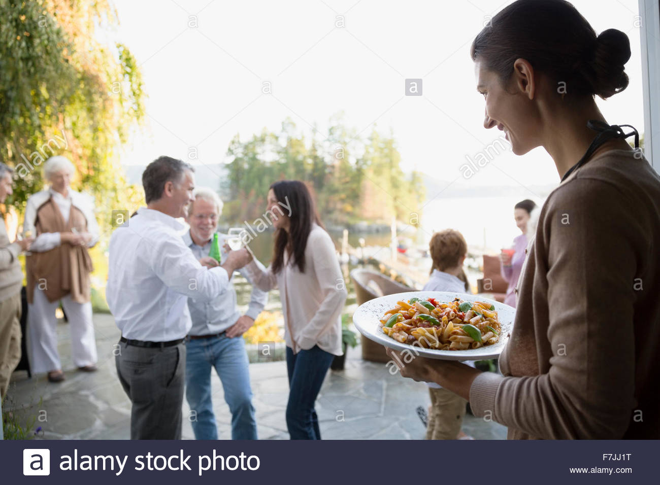 Woman serving food on patio - Stock Image
