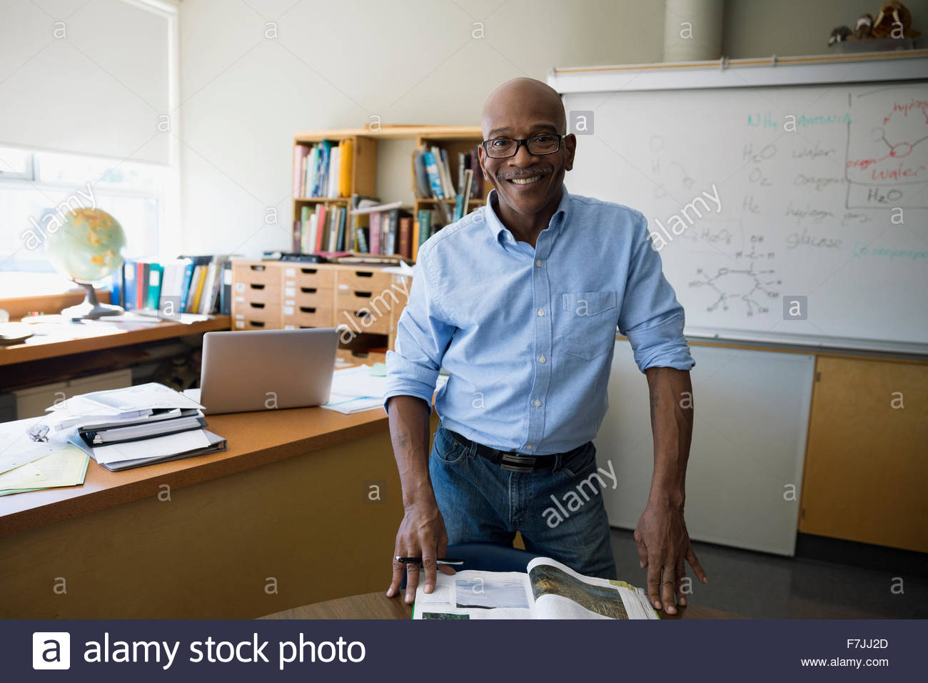 Portrait confident chemistry teacher with textbook in classroom - Stock Image