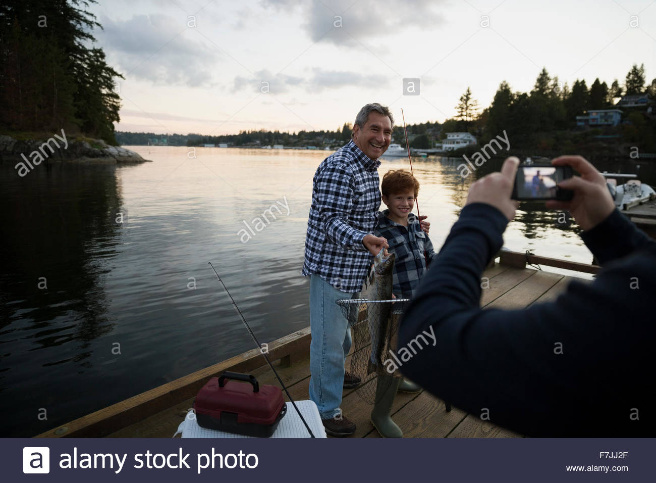 Grandfather and grandson posing caught fish lake dock - Stock Image