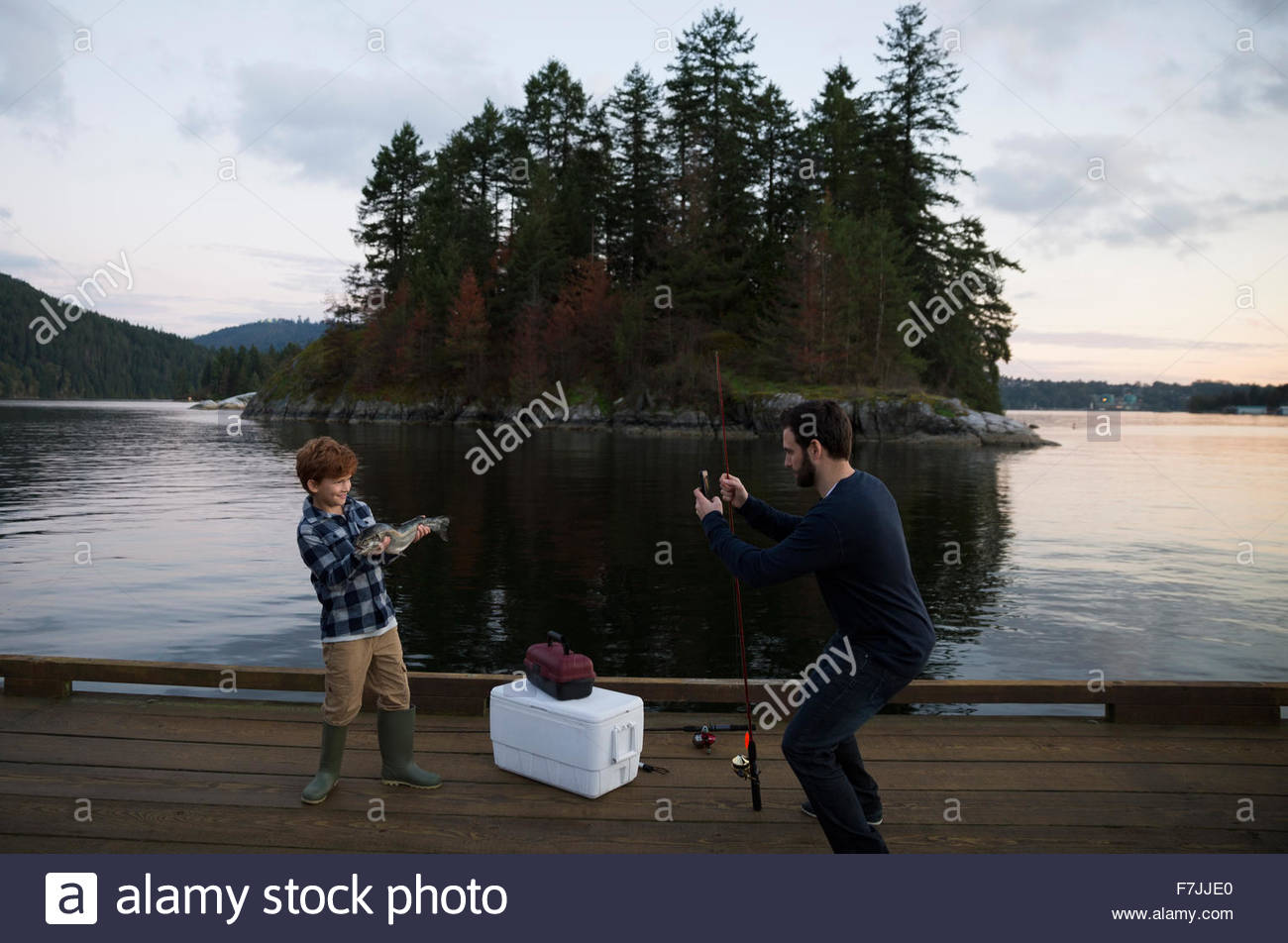 Father photographing son caught fish lake at sunset - Stock Image