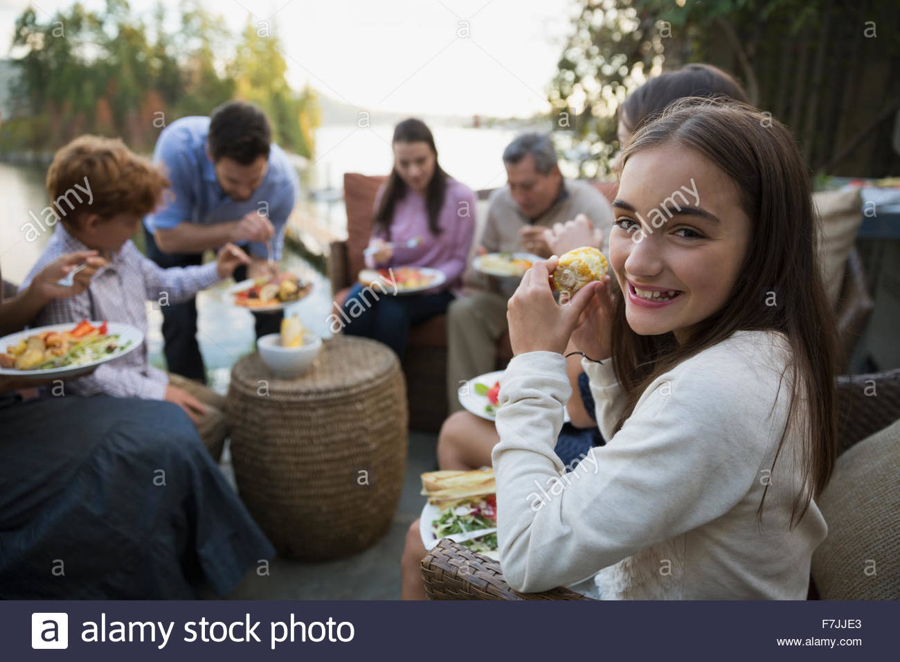 Portrait smiling girl eating with family on patio - Stock Image