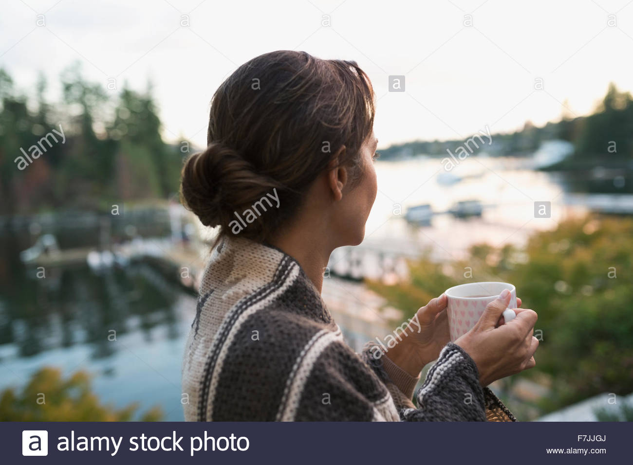 Serene woman drinking coffee looking at lake view - Stock Image