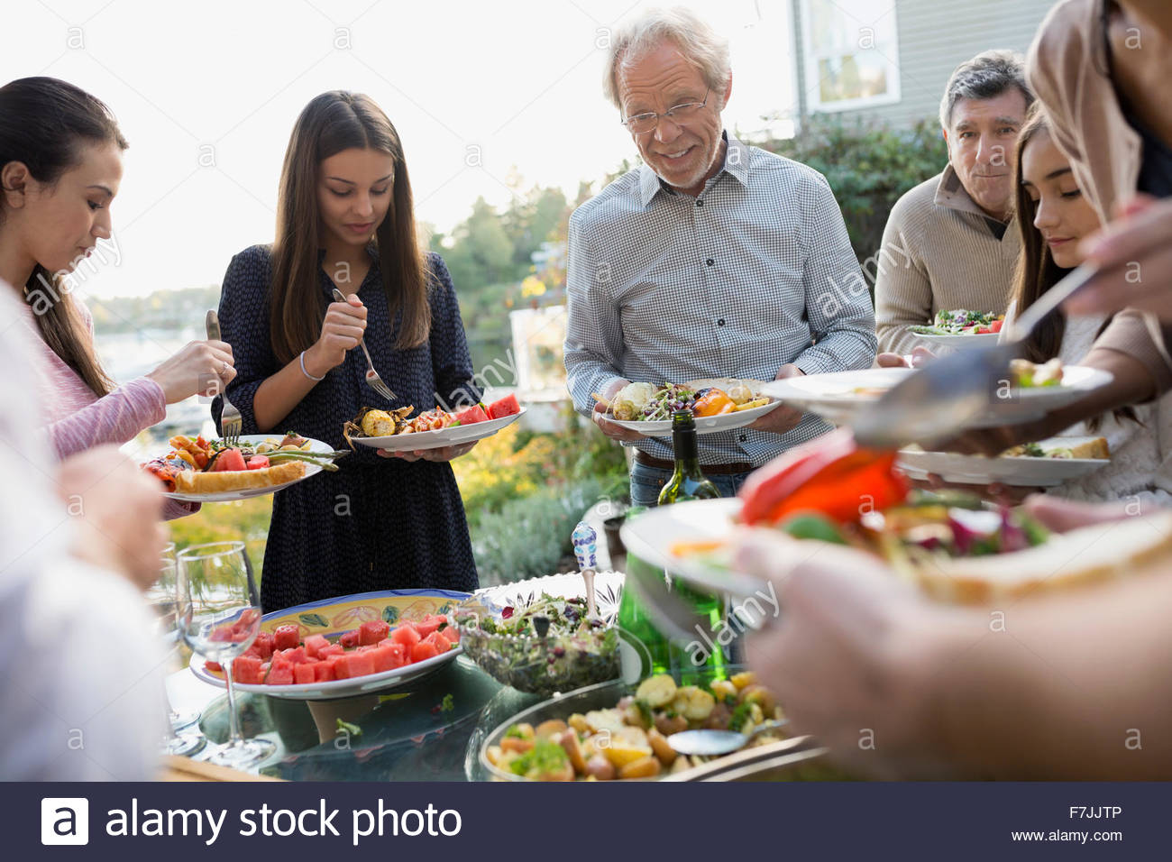 Multi-generation family serving food at buffet patio - Stock Image