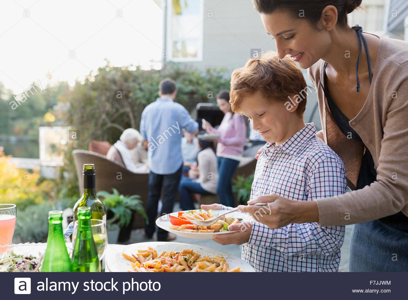 Mother helping serve son food at buffet patio - Stock Image