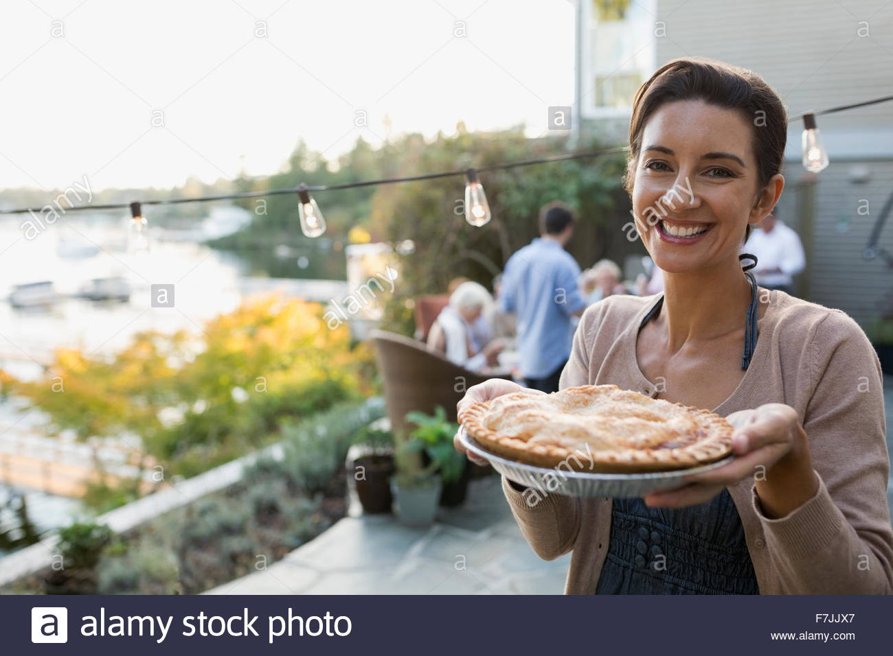 Portrait smiling woman serving homemade pie lakeside patio - Stock Image