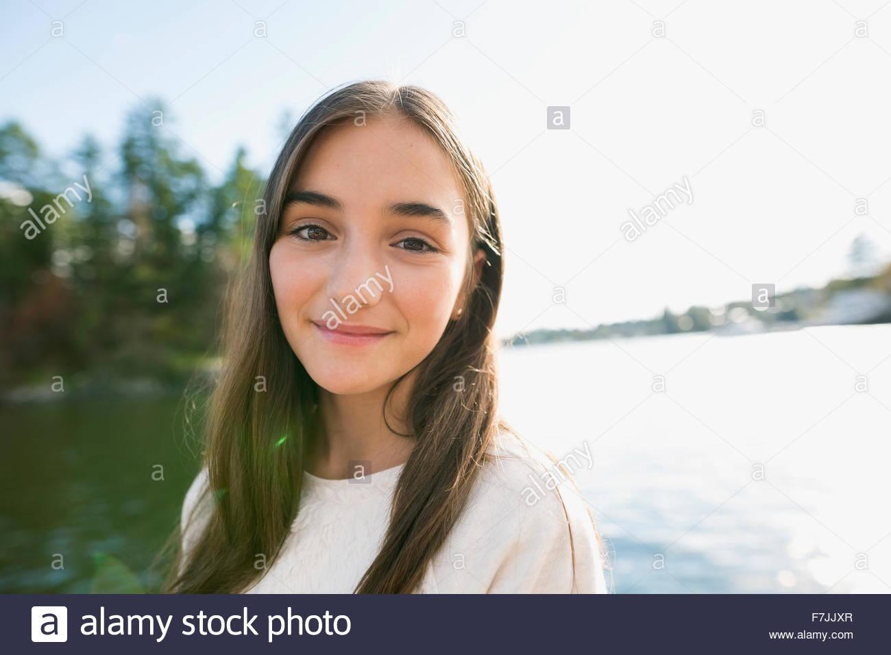 Portrait smiling brunette girl at lakeside - Stock Image
