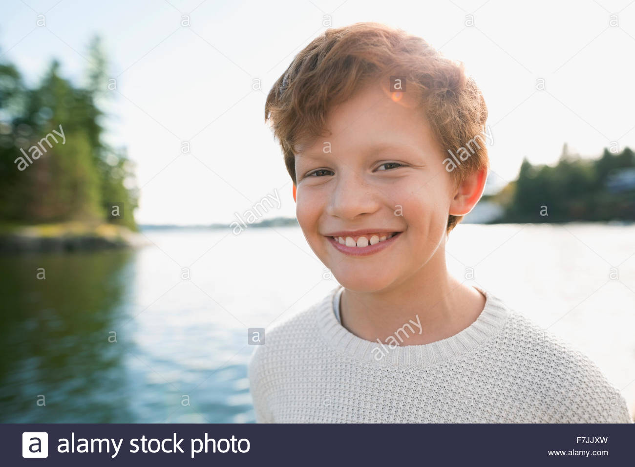 Portrait smiling boy with red hair at lakeside - Stock Image