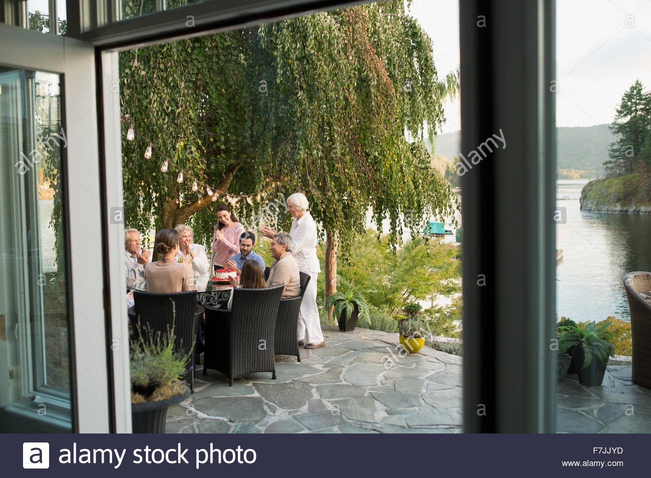 Family celebrating birthday on lakeside patio - Stock Image