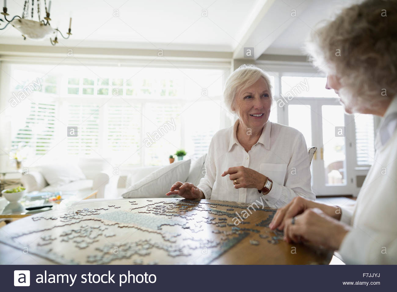 Senior women assembling jigsaw puzzle at dining table - Stock Image
