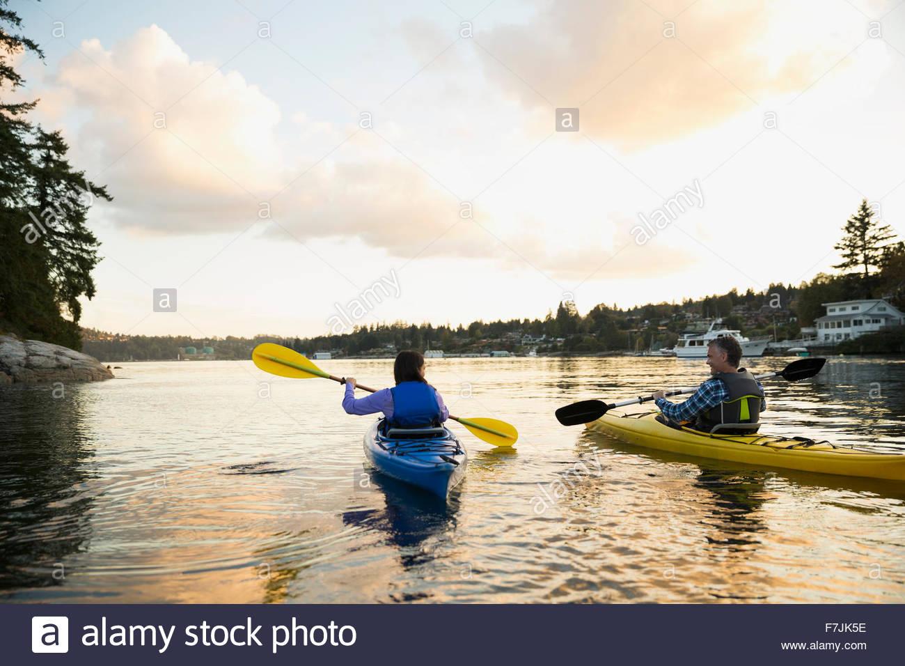 Couple kayaking on lake at sunset - Stock Image