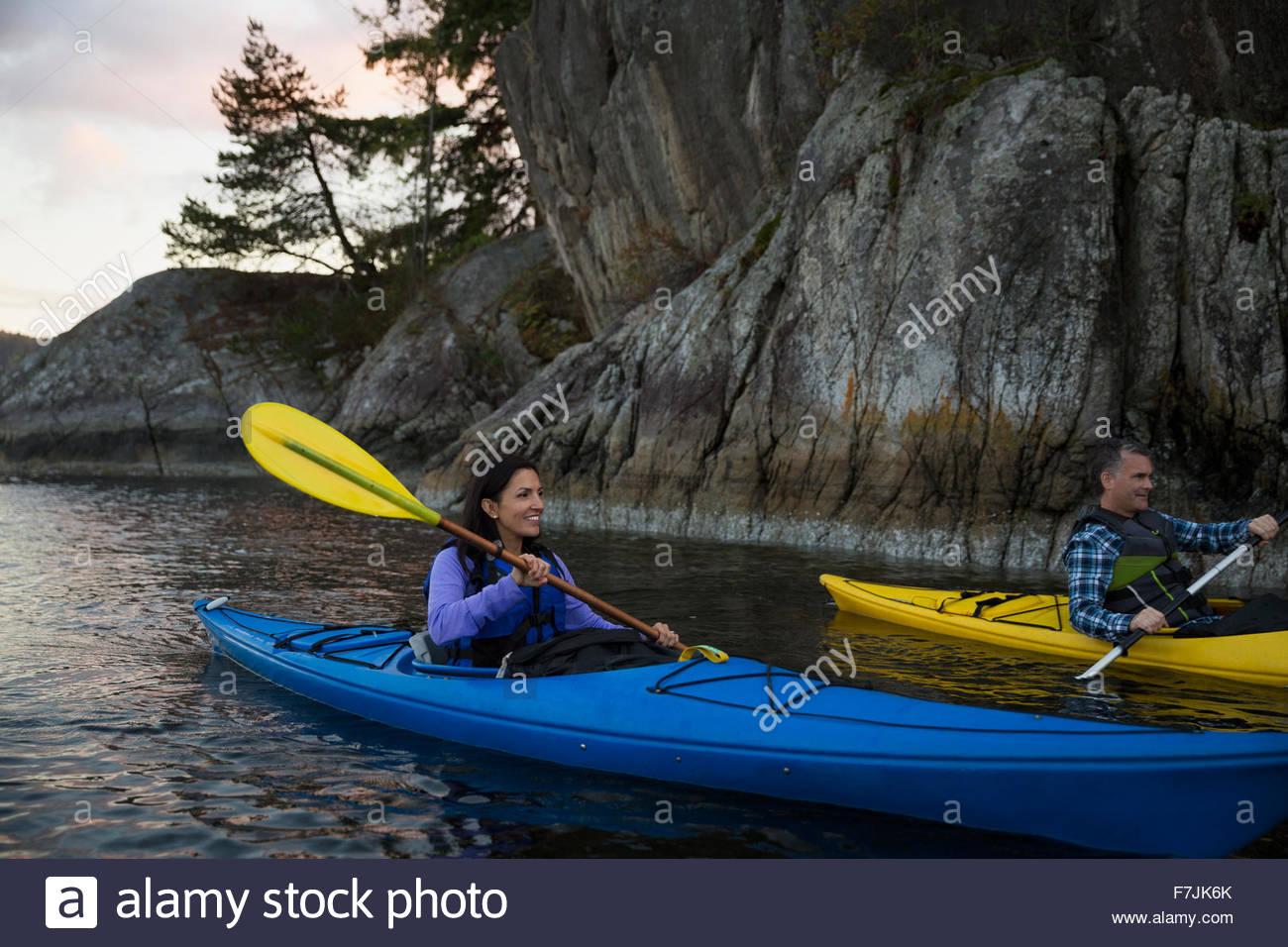 Couple canoeing on lake at sunset - Stock Image