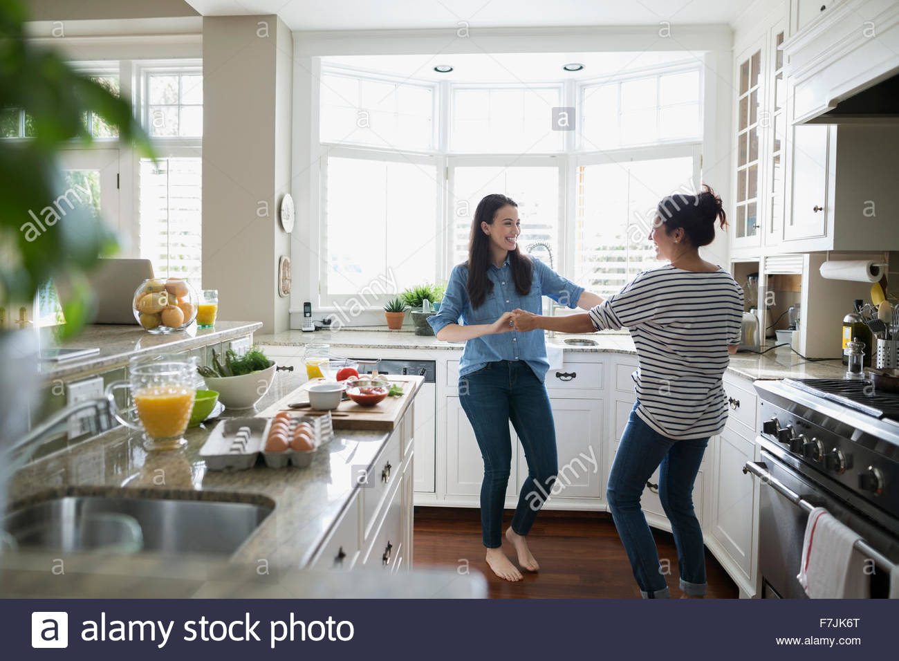 Mother and daughter dancing in kitchen - Stock Image