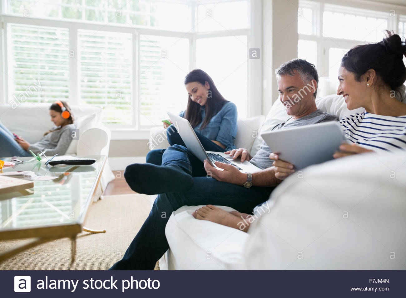 Family using wireless technology on living room sofa - Stock Image