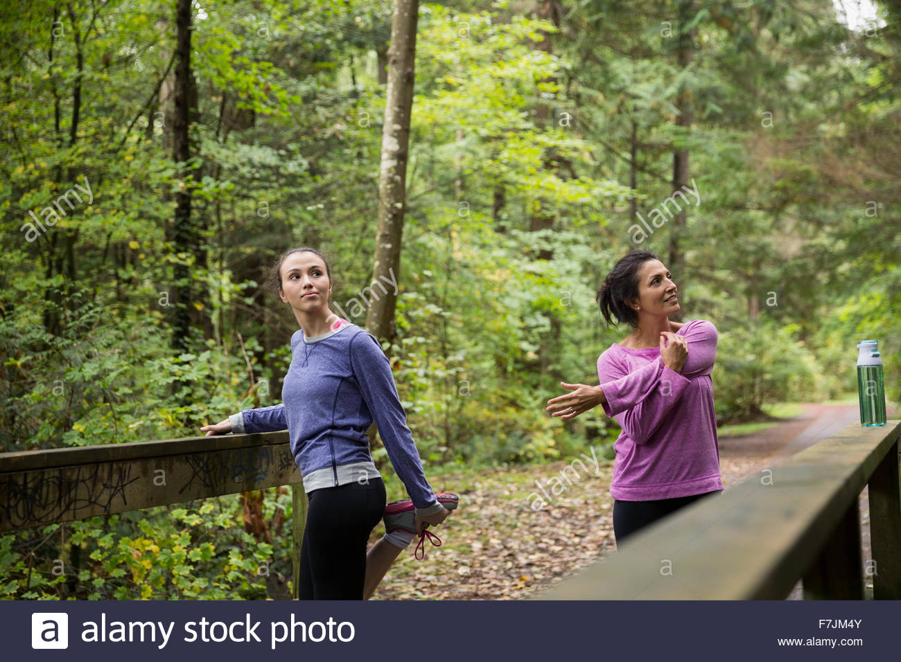 Mother and daughter stretching preparing for run woods - Stock Image